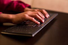 Afro child's hands using keyboard. Royalty Free Stock Photos
