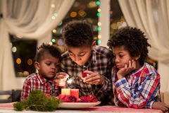 Afro children lighting Christmas candles. Boys light candles on Christmas. Holiday preparations in the evening. Decorating room for Christmas Royalty Free Stock Images