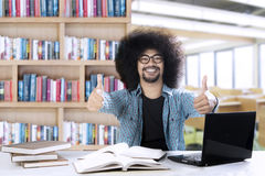 Afro college student showing thumbs up. Picture of an Afro college student looks happy while showing thumbs up in the classroom Royalty Free Stock Images