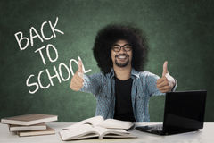 Afro college student with thumbs up. Picture of Afro male college student giving thumbs up while sitting with word of back to school on the chalkboard Royalty Free Stock Photos