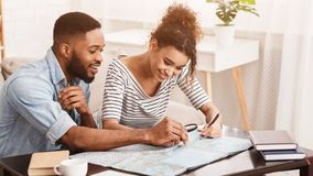 Afro Couple Planning Travel. Searching Best Route On Map. Using Magnifier royalty free stock image