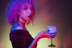 Afro dark woman holding an alcoholic mystery drink in halloween. Background Stock Images