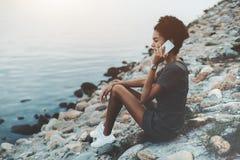 Afro dziewczyna opowiada na telefonie blisko rzeki Obrazy Stock