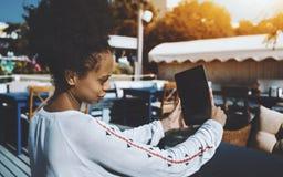 Afro dziewczyna z cyfrowym ochraniaczem w ulica barze Zdjęcia Stock