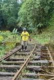 Afro-Ecuadorian man walking on a railroad bridge in the jungle. Afro-Ecuadorian man walking on an abandoned railroad bridge used by a homemade `ghost train` near Royalty Free Stock Images