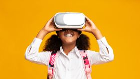 Free Afro Elementary Student Girl Using VR Headset, Yellow Background Stock Photos - 157580183