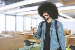 Afro facet patrzeje smartphone w sala lekcyjnej Fotografia Stock