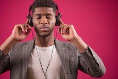 Afro facet słucha muzyka na hełmofonach z zamkniętymi oczami koncentrat na muzyce Zdjęcie Stock