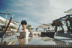 Afro- flicka i gatastång med den digitala minnestavlan Royaltyfri Fotografi