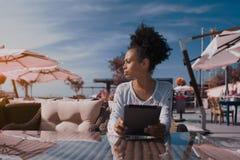 Afro- flicka i kafé med den digitala minnestavlan som åt sidan ser Royaltyfri Foto
