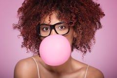 Afro- flicka som blåser bubbelgumballongen royaltyfri fotografi