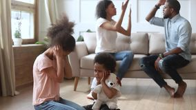 African frightened children covered ears not to hear parents quarrel. Afro frightened little kids sit on floor covered ears not to hear parents quarrel, couple stock video footage