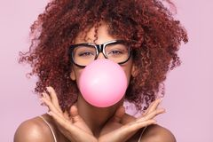 Afro girl blowing bubble gum balloon. Afro girl blowing a bubble gum balloon over pink background, looking at camera Royalty Free Stock Photo