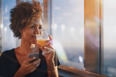 Afro girl with glass of juica and smartphone Royalty Free Stock Photo