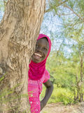 Afro girl playing hide-and-seek behind a filao tree, ten years old Royalty Free Stock Photography