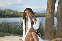 Free Afro Girl Poses Looking At The Camera With Long Black And Blonde Braids With A Lake In The Background Stock Image - 167948521