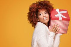 Afro girl posing with gift box, smiling. Beautiful african american girl with afro hairstyle holding gift box, smiling. Happy woman on yellow background royalty free stock photos