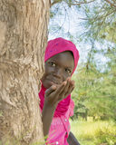 Afro girl sending a kiss from behind a filao tree, ten years old Stock Photos