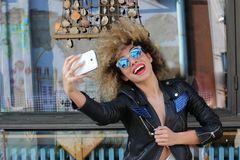 Afro girl with sunglasses posing. Happiness playful fun selfie smartphone Stock Photo