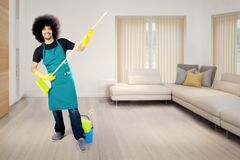 Afro gosposia bawić się gitarę miotła w domu Fotografia Stock
