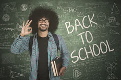 Afro guy shows ok sign with doodle. Afro guy showing ok sign while holding book with doodle and back to school text on chalkboard Stock Photo