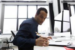 Afro het Amerikaanse zakenman neemt van maken terwijl het zitten bij zijn bureau nota Royalty-vrije Stock Fotografie