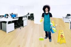 Afro janitor with wet floor sign in office. Picture of Afro male janitor carrying a broom and bucket while standing with a wet floor sign in the office Royalty Free Stock Photography