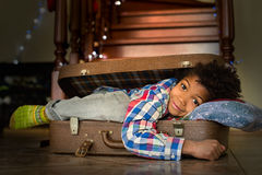 Afro kid's energetic morning smile. Boy waking up inside suitcase. Afro kid's energetic morning smile. New day new journey. Time for adventures Royalty Free Stock Photography