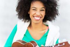 Afro kobieta bawić się ukulele Zdjęcia Royalty Free