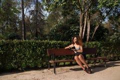 Afro kobieta czyta książkę na ławce Zdjęcia Royalty Free