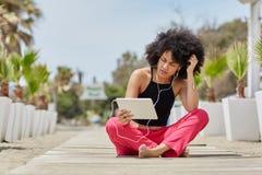 Afro kobiety amerykański obsiadanie krzyżujący iść na piechotę outside używa pastylkę Zdjęcia Stock
