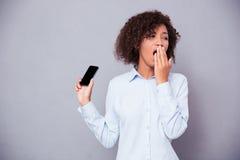 Afro kobiety amerykański ziewanie podczas gdy trzymający smartphone Obrazy Royalty Free