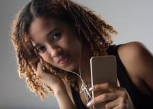 Afro Kolumbijskiej dziewczyny słuchająca muzyka na jej mądrze telefonie Zdjęcia Royalty Free