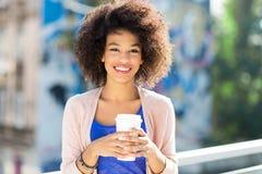 Afro- kvinna med kaffe som går Arkivbild