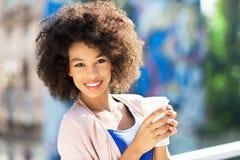 Afro- kvinna med kaffe som går Royaltyfria Foton