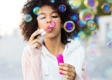 Afro- kvinna som blåser såpbubblor Arkivbild