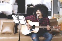 Afro mężczyzna bawić się gitarę w domu Obrazy Royalty Free
