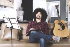 Afro mężczyzna komponuje piosenkę w domu Zdjęcia Stock