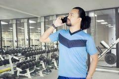 Afro mężczyzna z smartphone w sprawności fizycznej centrum Fotografia Stock