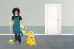 Afro maid with a caution sign in hotel Stock Photo