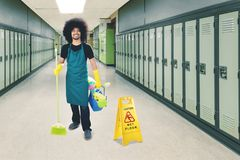 Afro maid standing with a wet floor sign. Image of male janitor holding a broom and bucket while standing with a wet floor sign in the school corridor Royalty Free Stock Photography