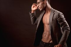 Afro male model with nacked torso and suit jacket wearing glasses. Side view cropped photo of afro male model with nacked torso and suit jacket wearing glasses Royalty Free Stock Photography