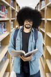 Afro male student reading a book at library. Portrait of Afro male student reading a book while standing in the library Stock Photo