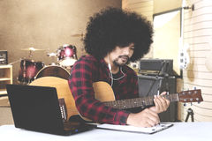 Afro man composing song in music studio. Afro man composing a song and writing on clipboard while listening music on earphone in music studio Stock Images