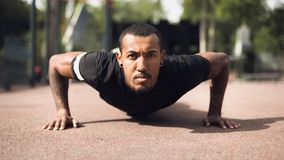 Afro Man Doing Push Ups On Sports Ground. Working Out In The Morning stock photos