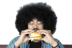 Afro man eating a delicious hamburger. Portrait of afro man eating delicious hamburger in the studio, isolated on white background Stock Photography