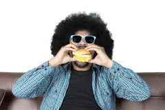 Afro man eating yummy hamburger. Portrait of afro man eating yummy hamburger while sitting on the brown couch in studio Royalty Free Stock Photos