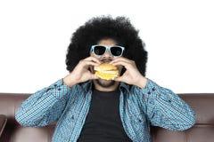 Afro man eating yummy hamburger Royalty Free Stock Photos