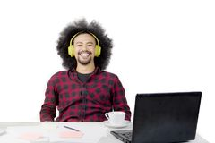 Afro man with headphone on studio. Afro man looks happy while listening music with a headphone and studying with a laptop on studio Stock Photography