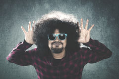 Afro man with jokes expression. Young Afro man with curly hair, wearing sunglasses and showing jokes expression Royalty Free Stock Image